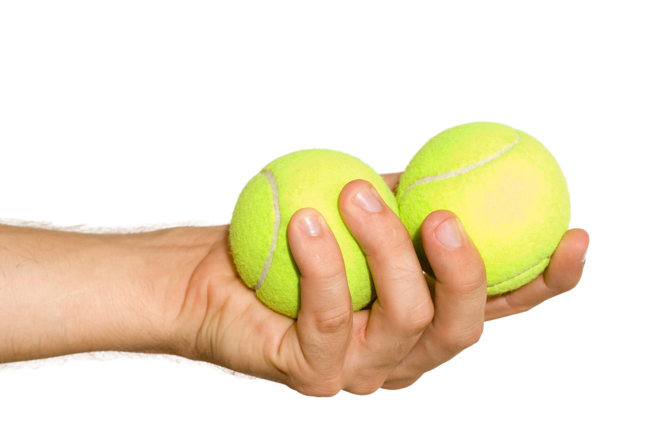 mão segurando duas bolas de tênis
