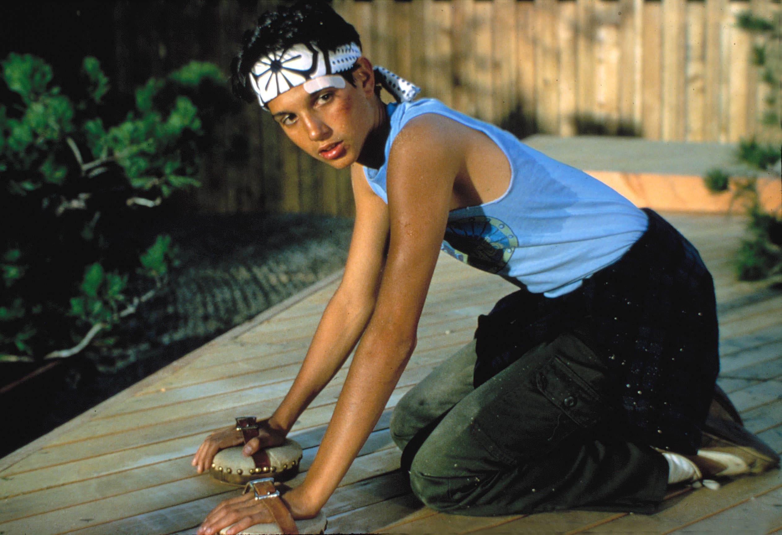 """Ralph Macchio cleaning a deck in """"The Karate Kid"""""""
