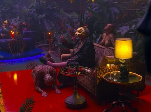 One of the VIPs sits on a couch with his foot propped up on a kneeling woman in body paint; another body-painted woman stands behind the couch with her eyes closed