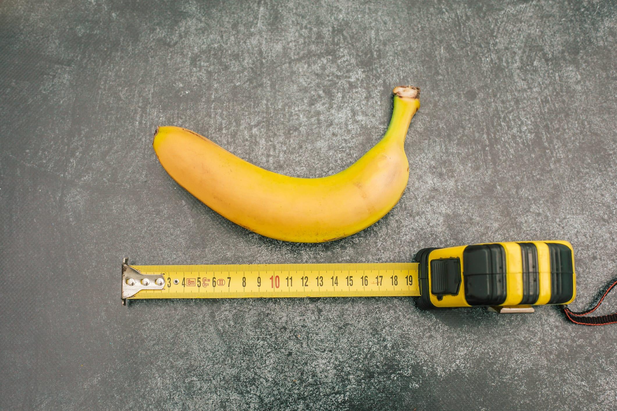 uma banana ao lado de uma fita métrica