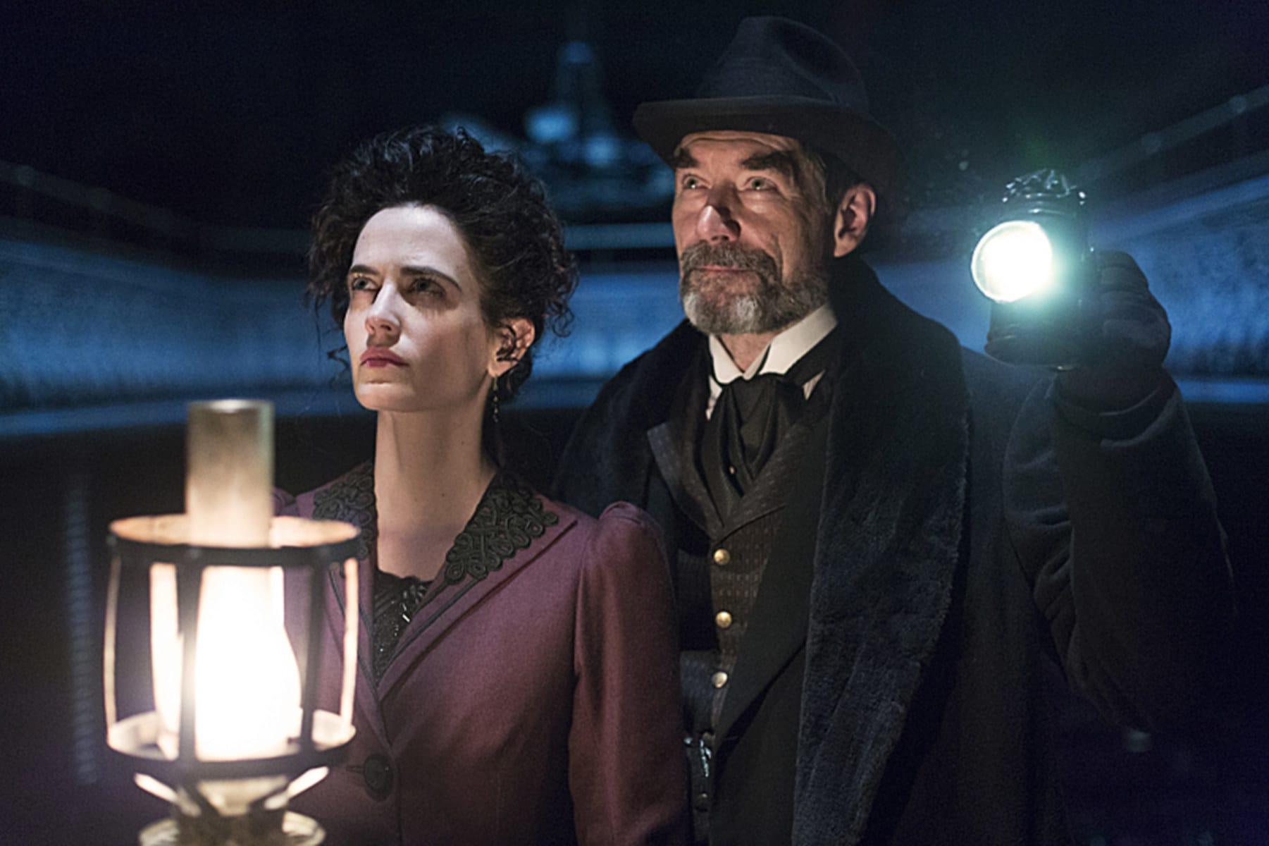 Imagem da série Penny Dreadful mostrando a personagem Vanessa Ives e o personagem Sir Malcom Murray. Ambos seguram lampiões.