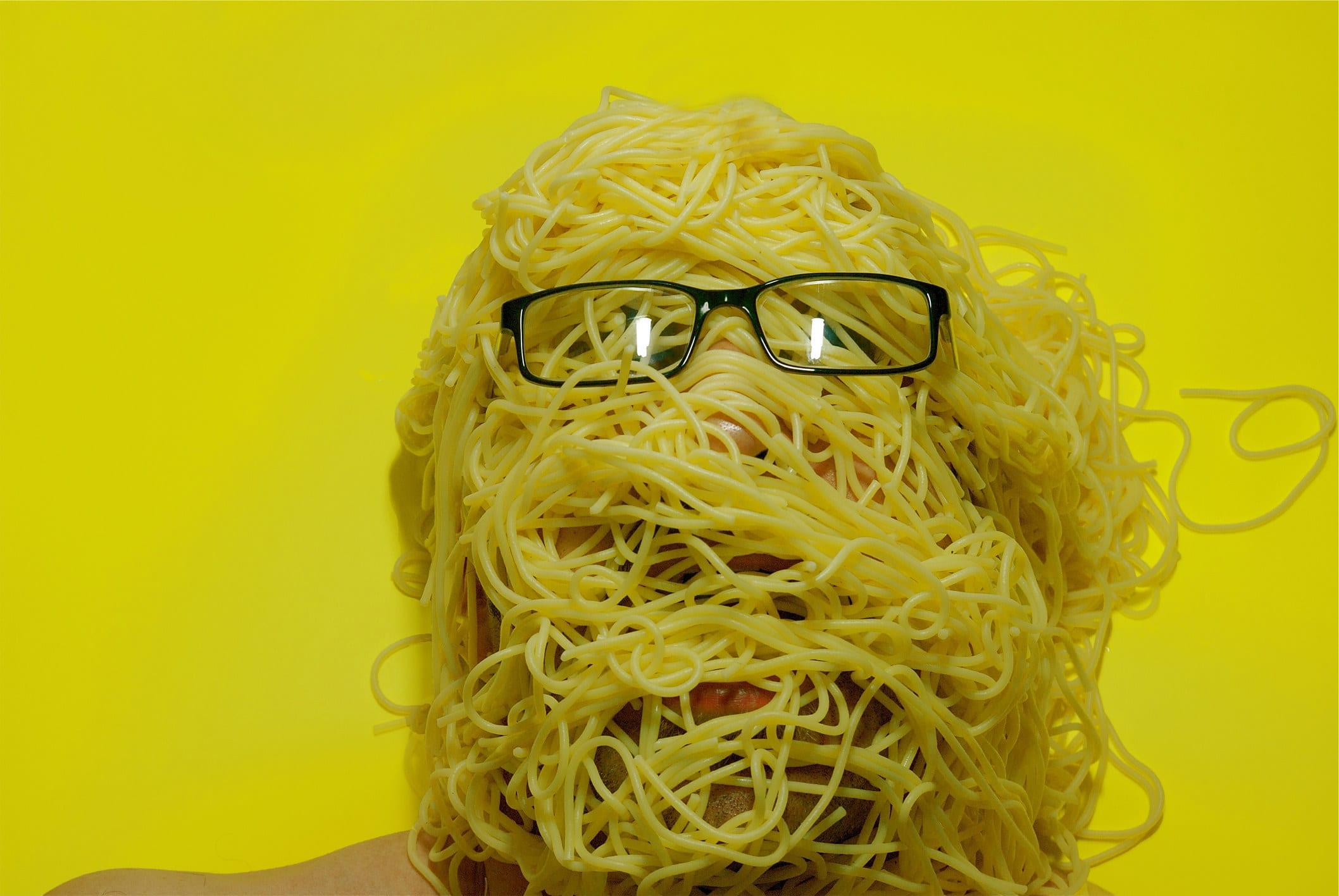 person with their head covered in cooked spaghetti noodles