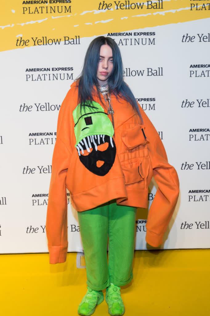 Billie no tapete vermelho com um moletom laranja largo e calça e tênis verde