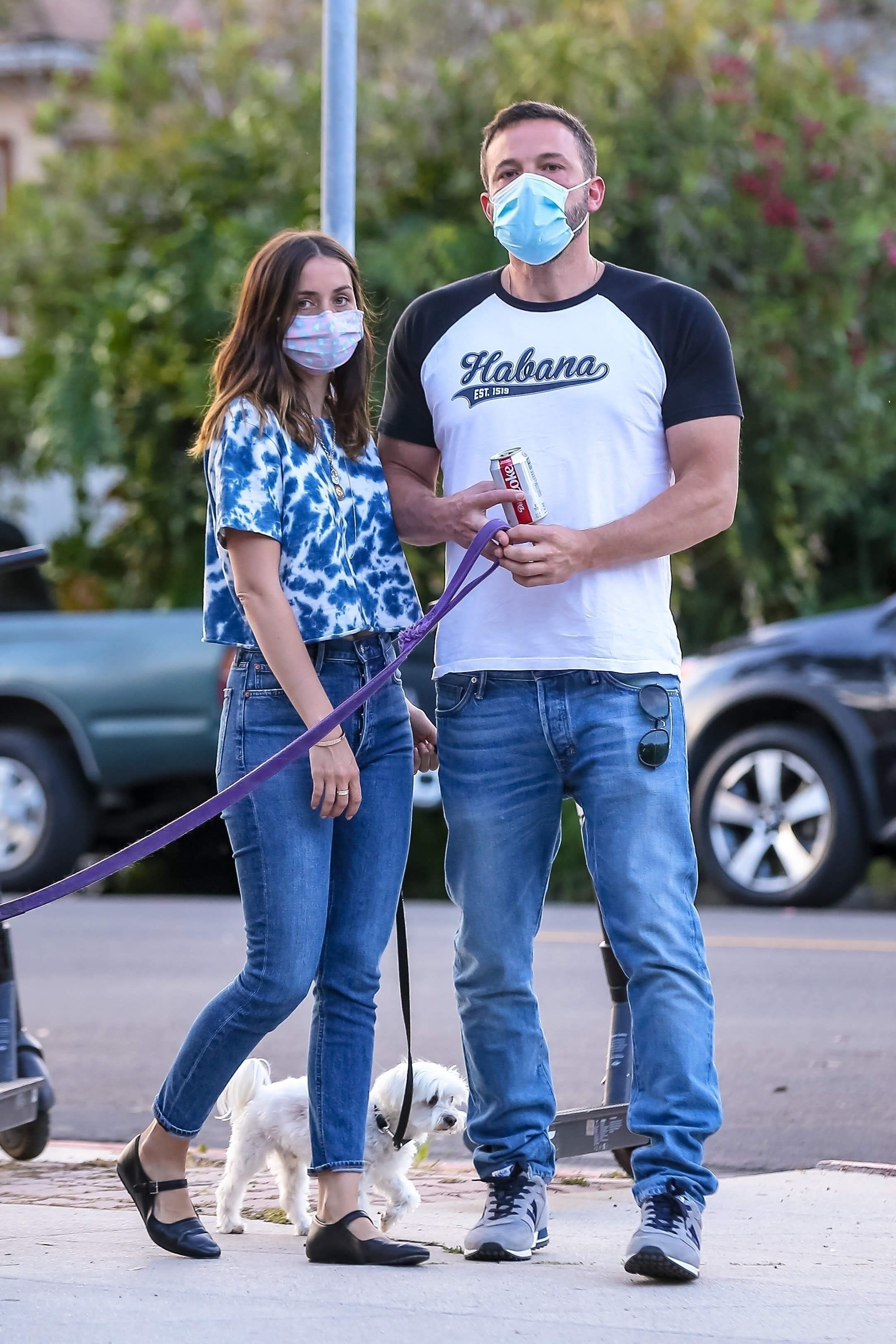 Foto de Ben Affleck e Ana de Armas andando com o cachorro deles.
