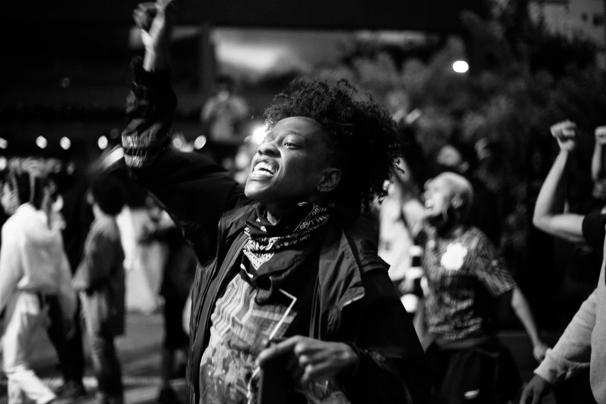 Cena de protesto com pessoas com braços erguidos, uma pessoa em primeiro plano com bandana no pescoço, gritando.