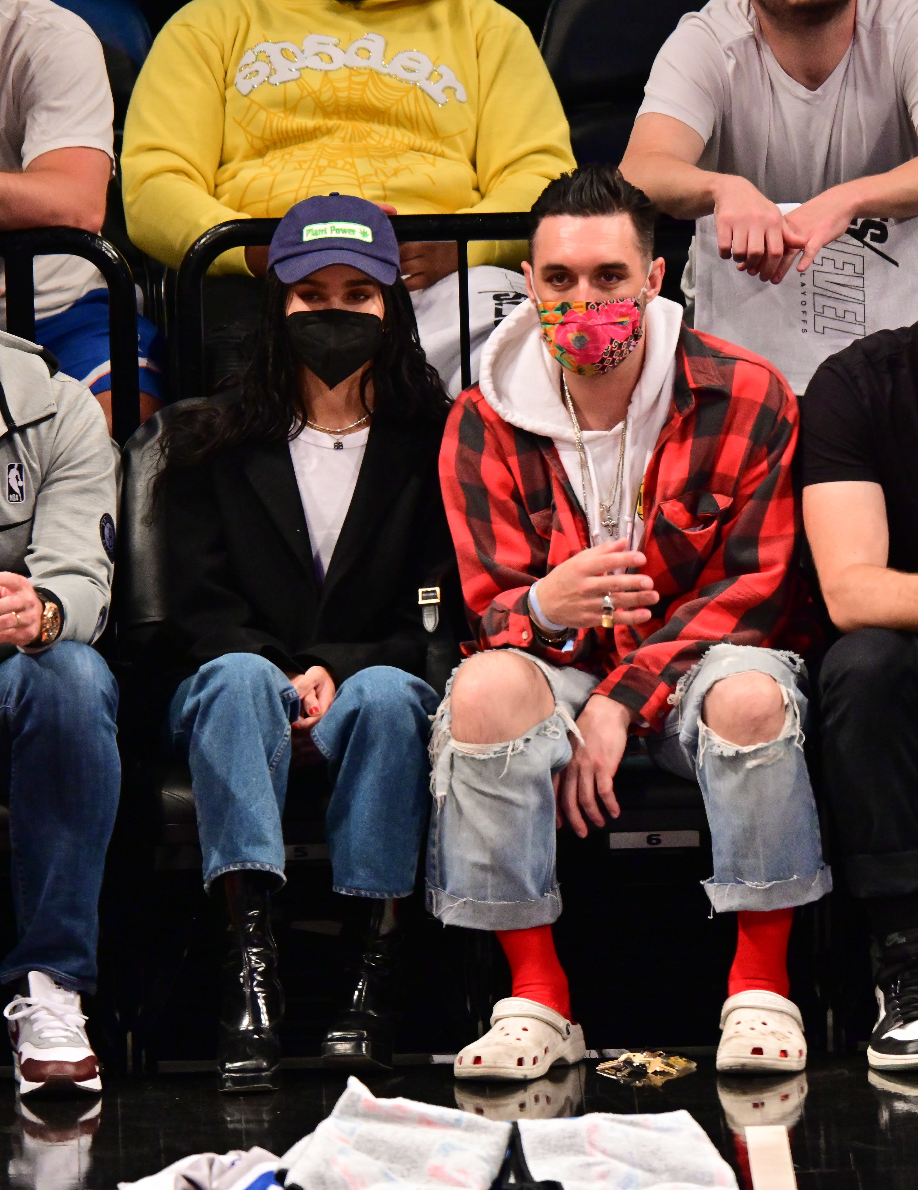 Zoe sitting courtside in jeans boots t-shirt cardi hat and mask