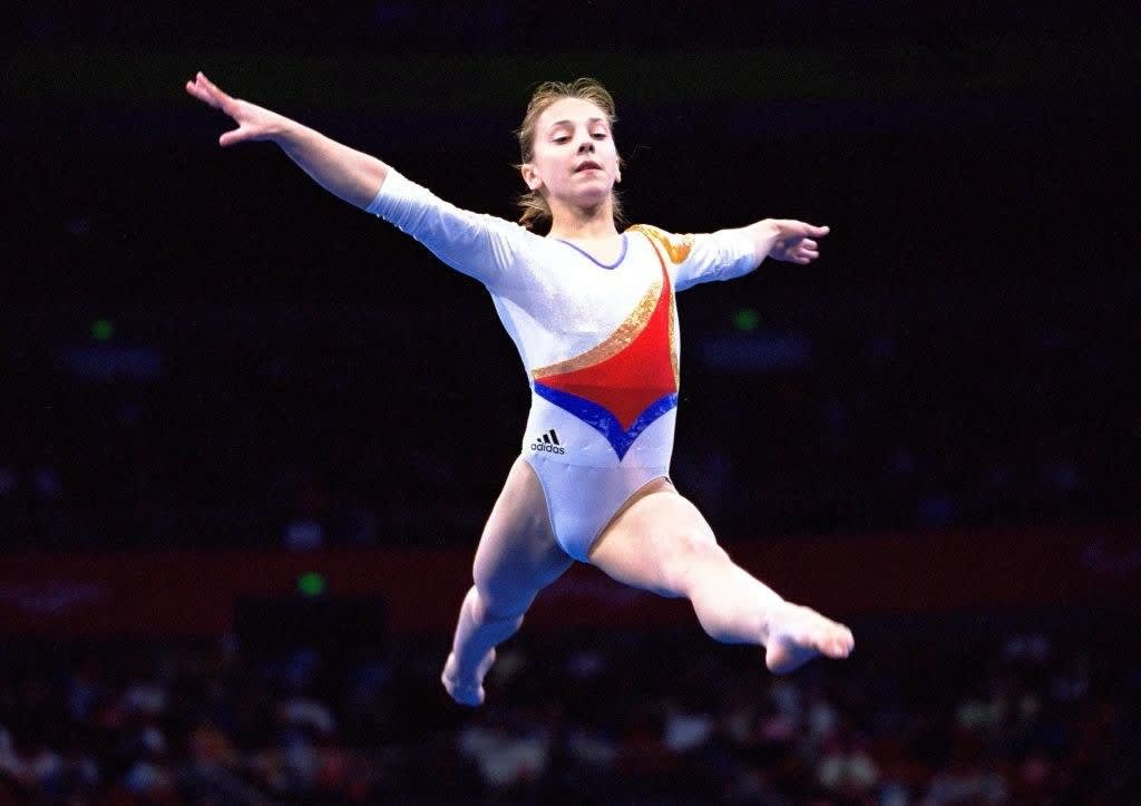 Andreea Răducan jumping mid air in her gymnastics routine at the 2000 olympics