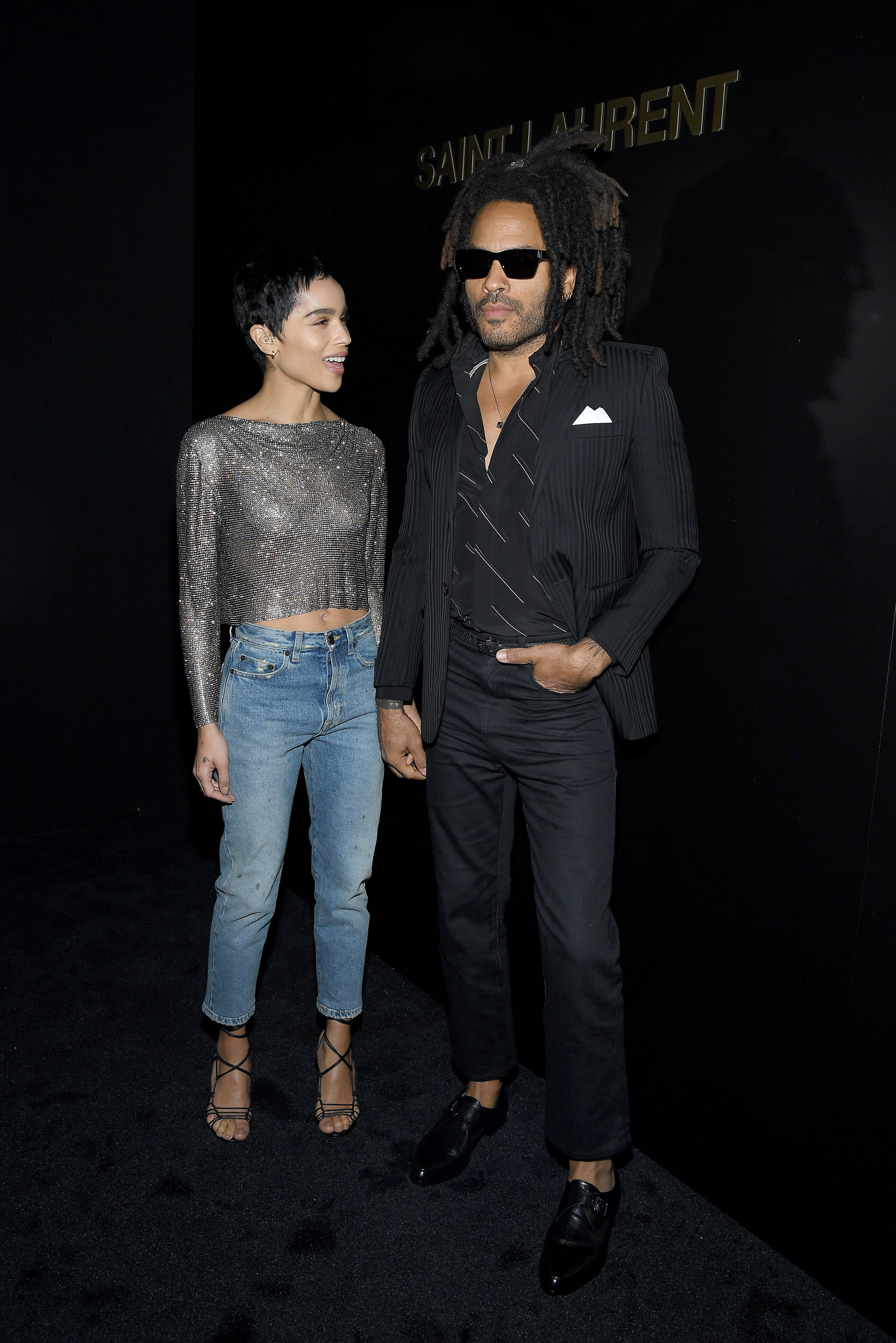 Zoe and Lenny Kravitz pose, she wears jeans a sparkling top strappy heels