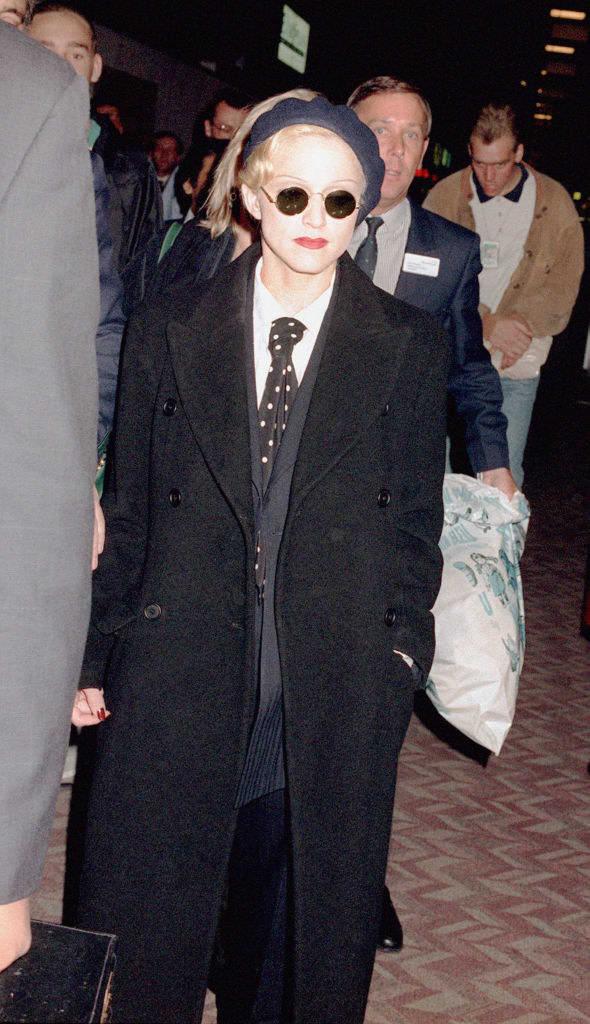 Madonna de terno e um sobretudo preto