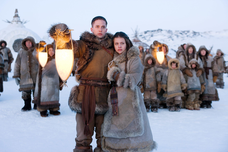 Jackson Rathbone and Nicola Peltz wearing big coats in the snow
