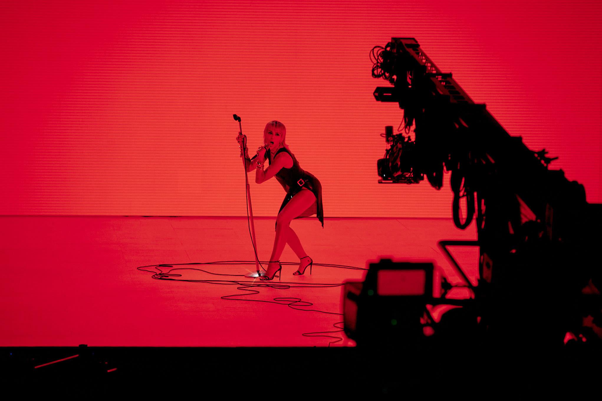 Miley cantando em um cenário vermelho e preto