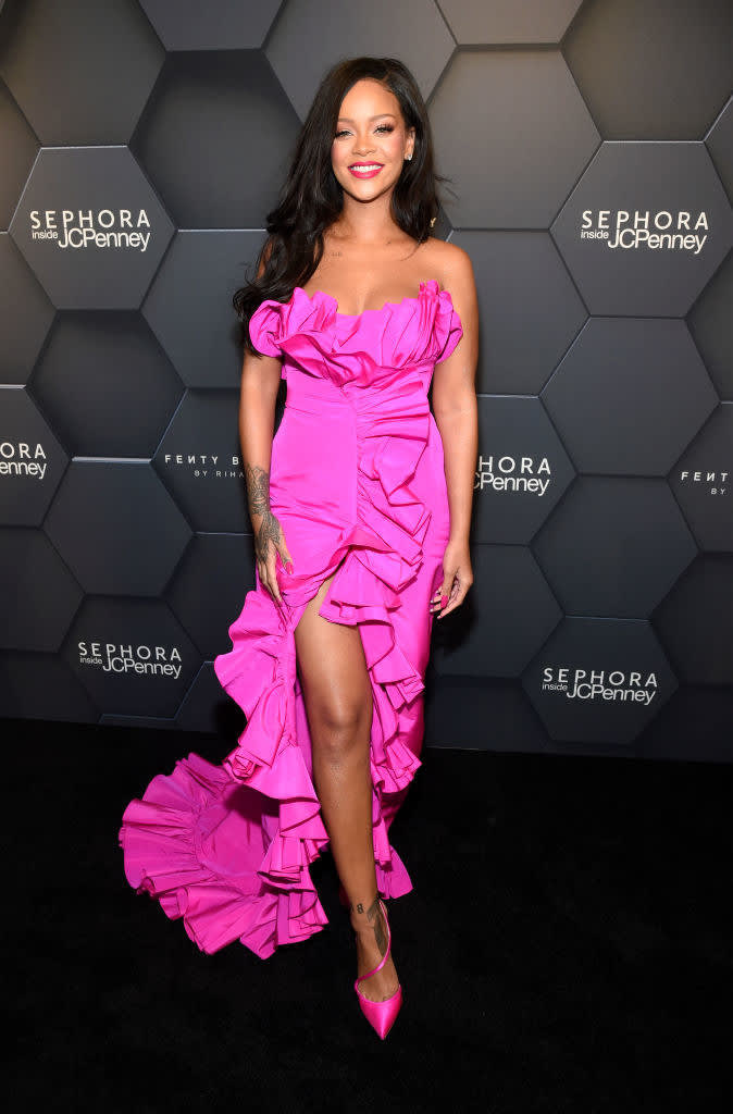 Rihanna on the red carpet, wearing a pink gown with a high slit