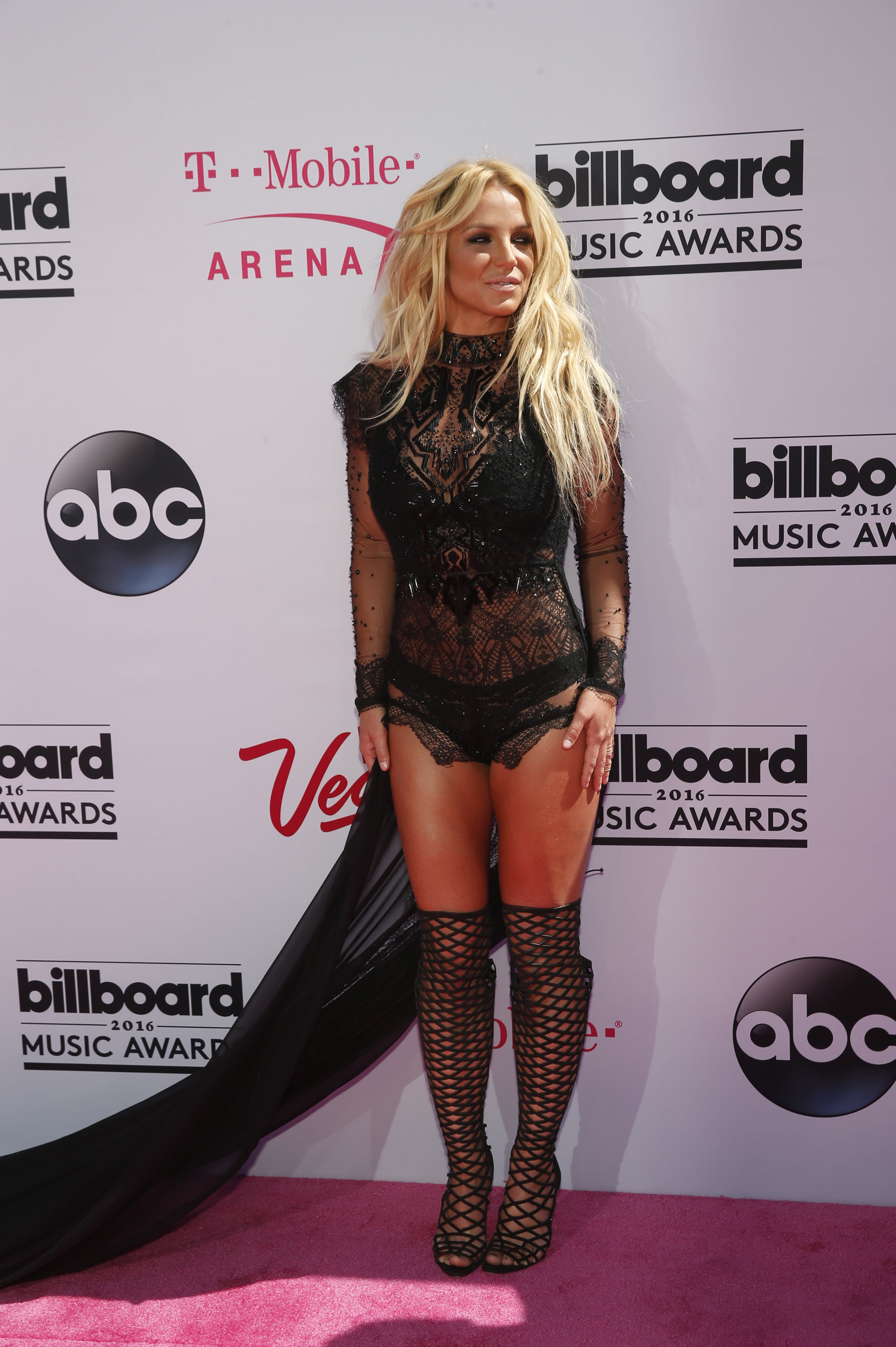 Britney posing on the red carpet at the 2016 Billboard Music Awards in a lacy see-through dress and matching boots
