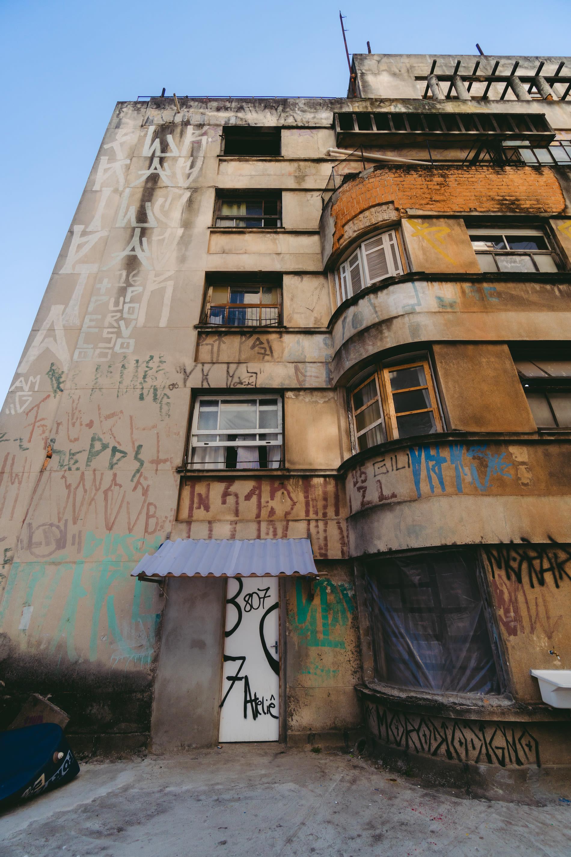 Visão externa da Ocupação 9 de Julho em um andar alto, prédio cheio de pixações contra céu azul.