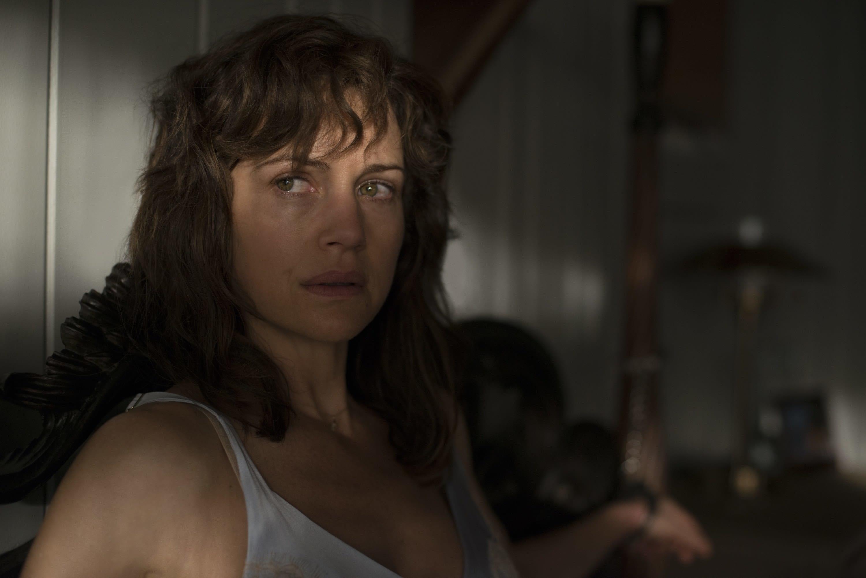 Imagem do filme Jogo Perigoso que mostra a personagem presa à sua cama com um olhar tenso no rosto.