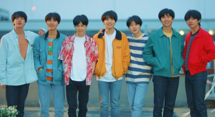 BTS stand in a row wearing casual clothes; they all have dark hair
