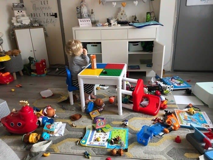 Criança sentada na mesinha comendo enquanto o chão está cheio de brinquedos.