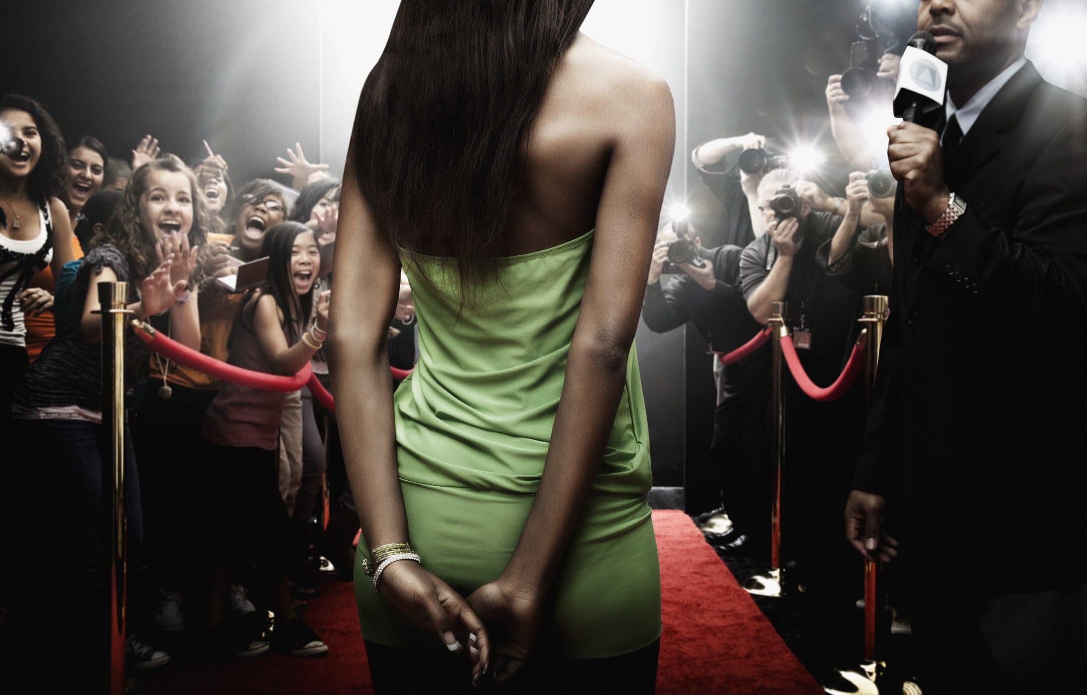 montagem de mulher andando no tapete vermelho, público gritando, fotógrafos fotografando e repórter entrevistando