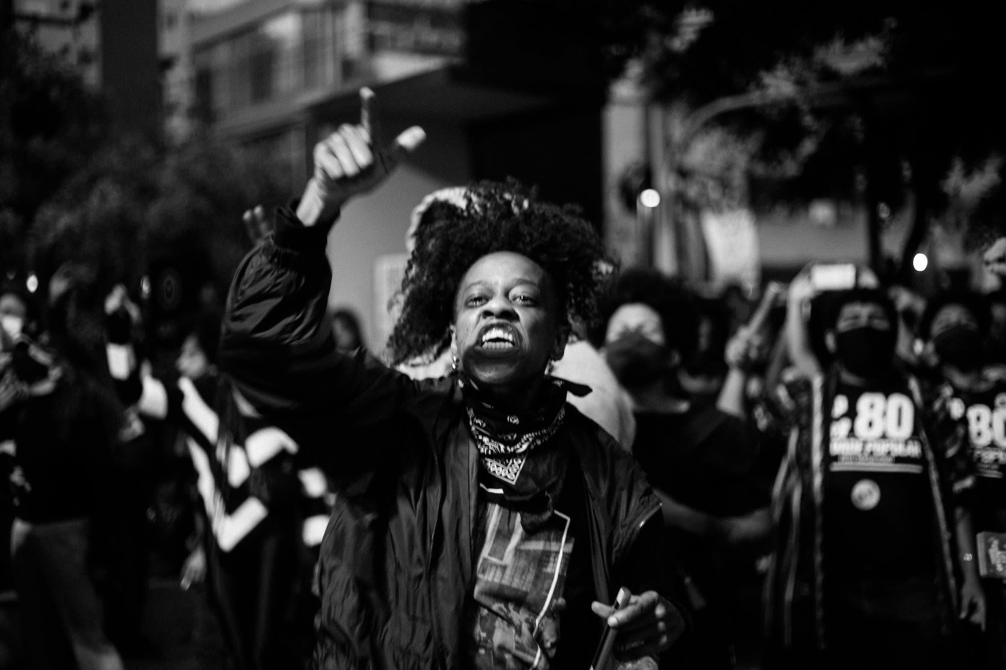 Cena de protesto com pessoas com braços erguidos, uma pessoa em primeiro plano com bandana no pescoço, gritando e apontando dedo.