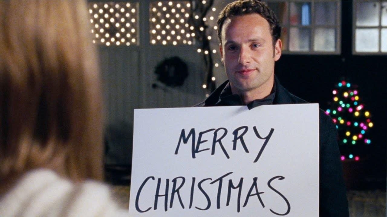 """Foto de um homem em um filme segurando uma placa de """"Feliz Natal"""""""