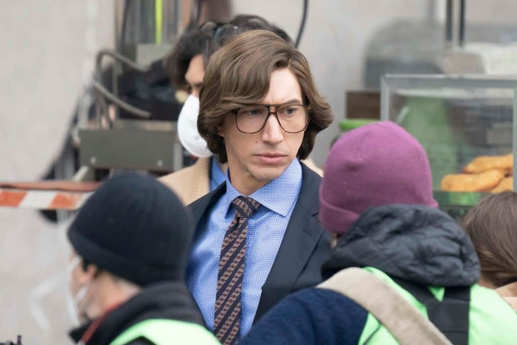 Adam as Maurizio posing in a suit and eyeglasses
