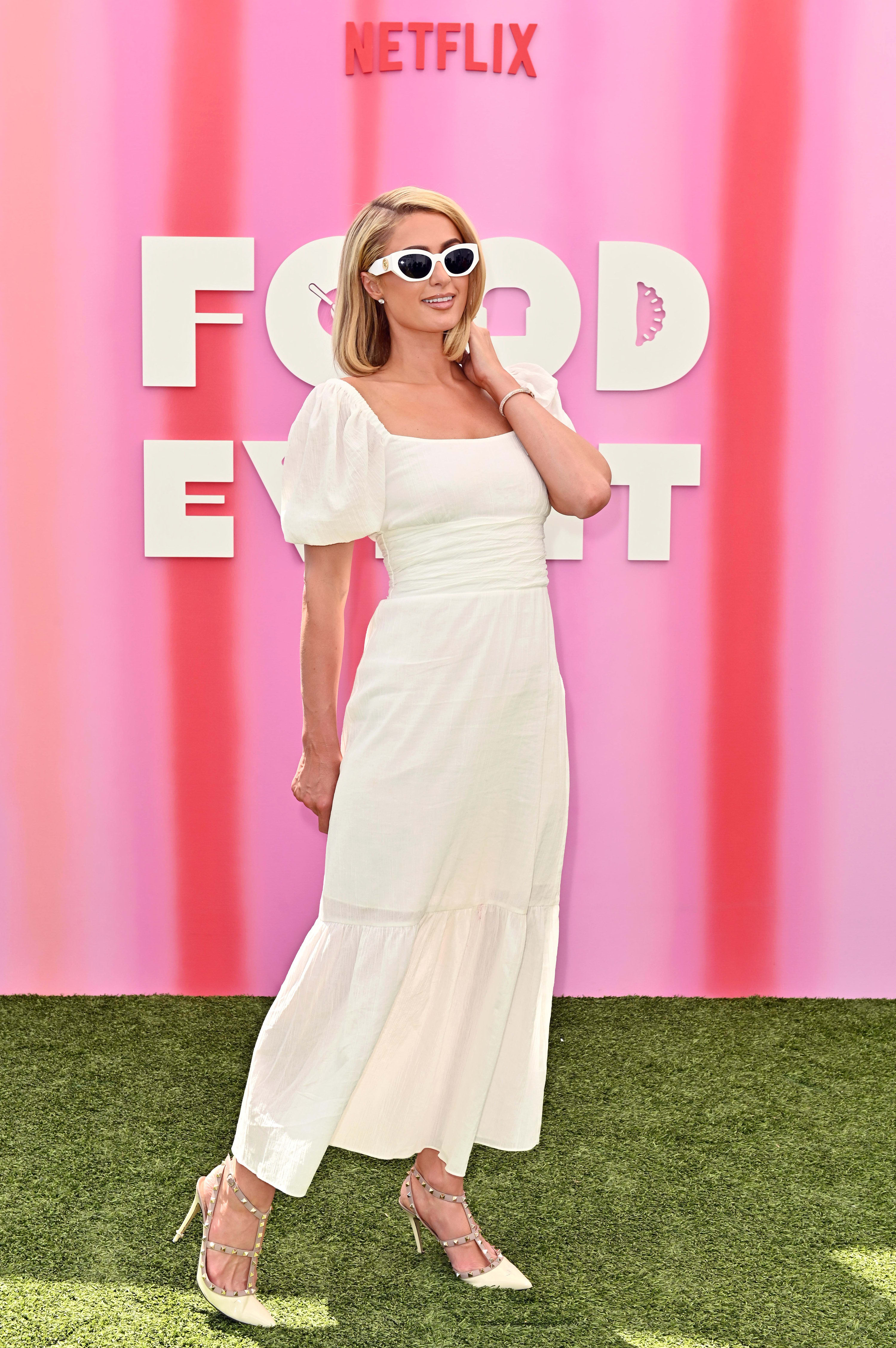 Paris wears a simple white dress with puffy short sleeves, sunglasses, and jeweled heels.
