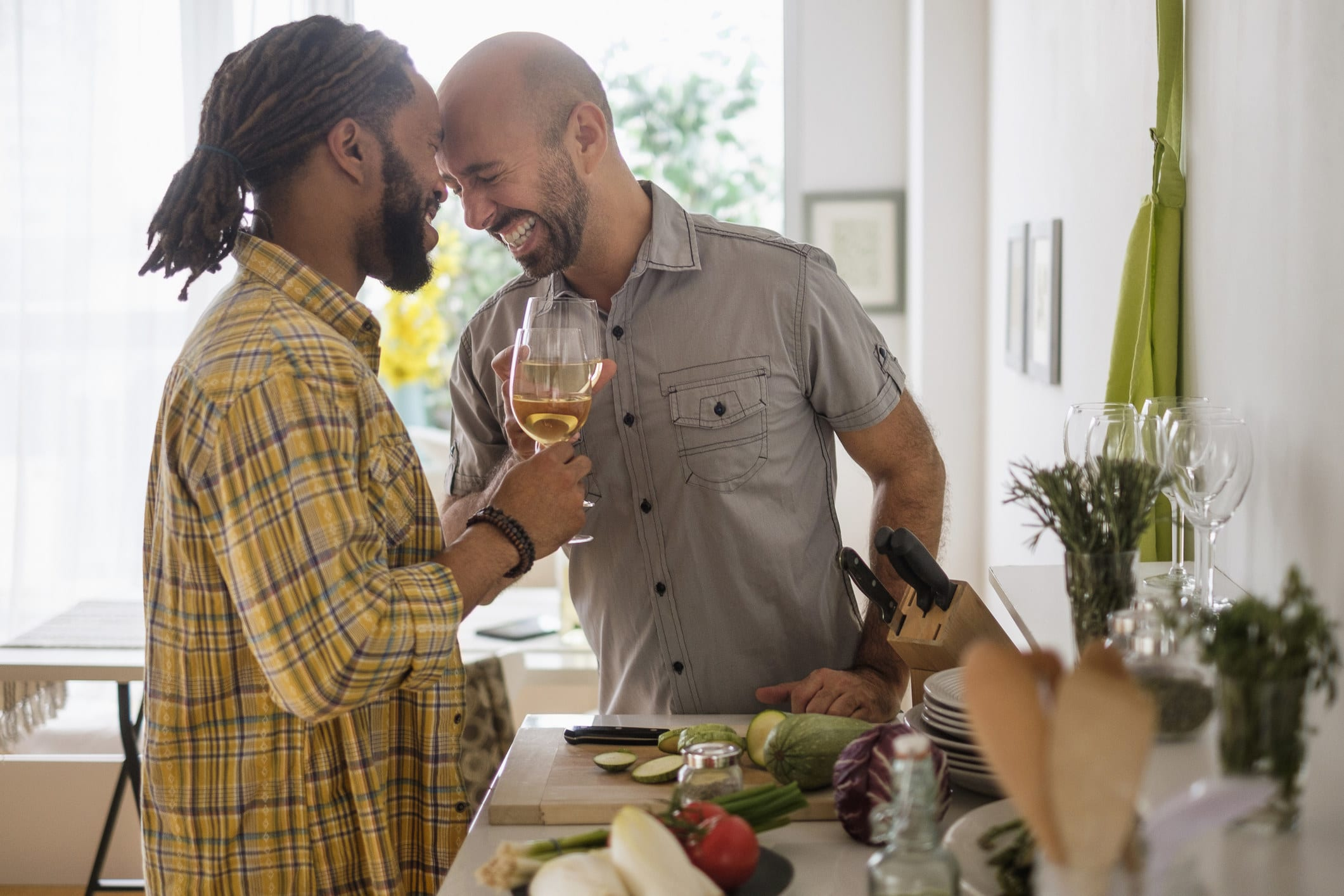 Gay couple laughing over wine in the kitchen