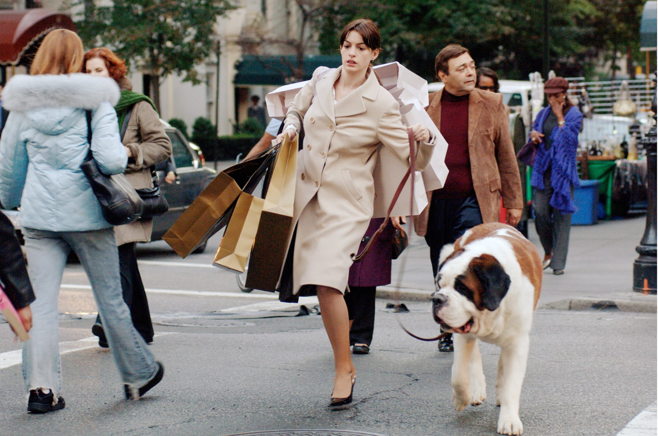 """Anne Hathaway wearing heels while walking a dog and carrying a bunch of shopping bags in """"The Devil Wears Prada"""""""