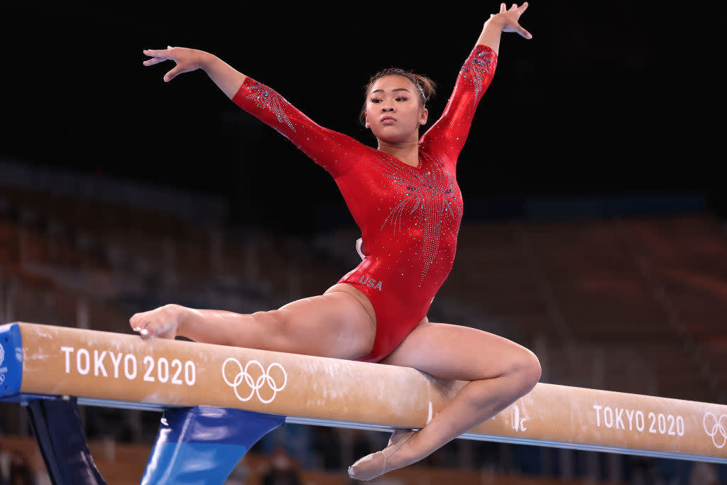 Suni Lee posing on the balance beam with her hands in the air