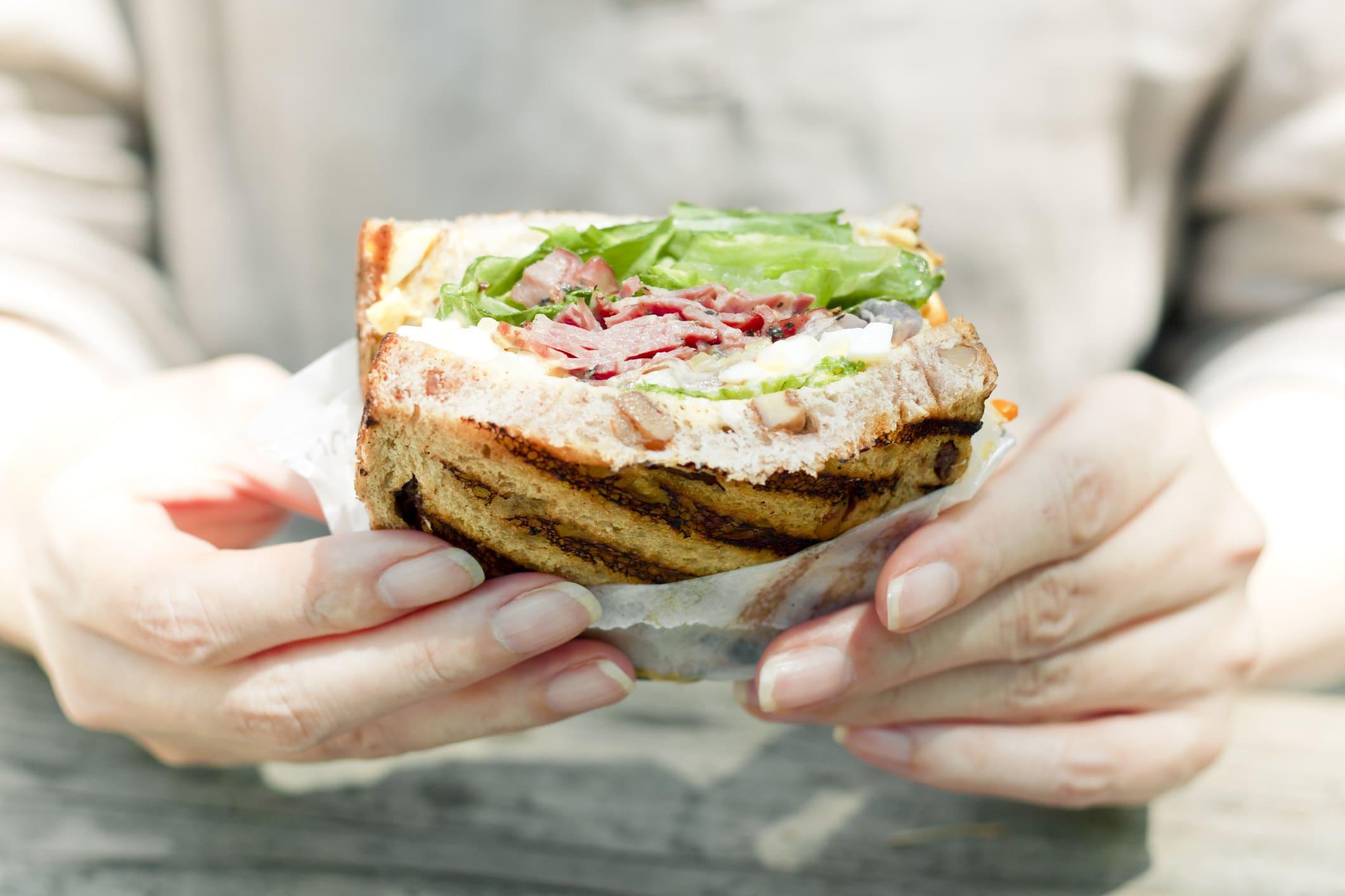 uma pessoa segurando um sanduíche prestes a comê-lo