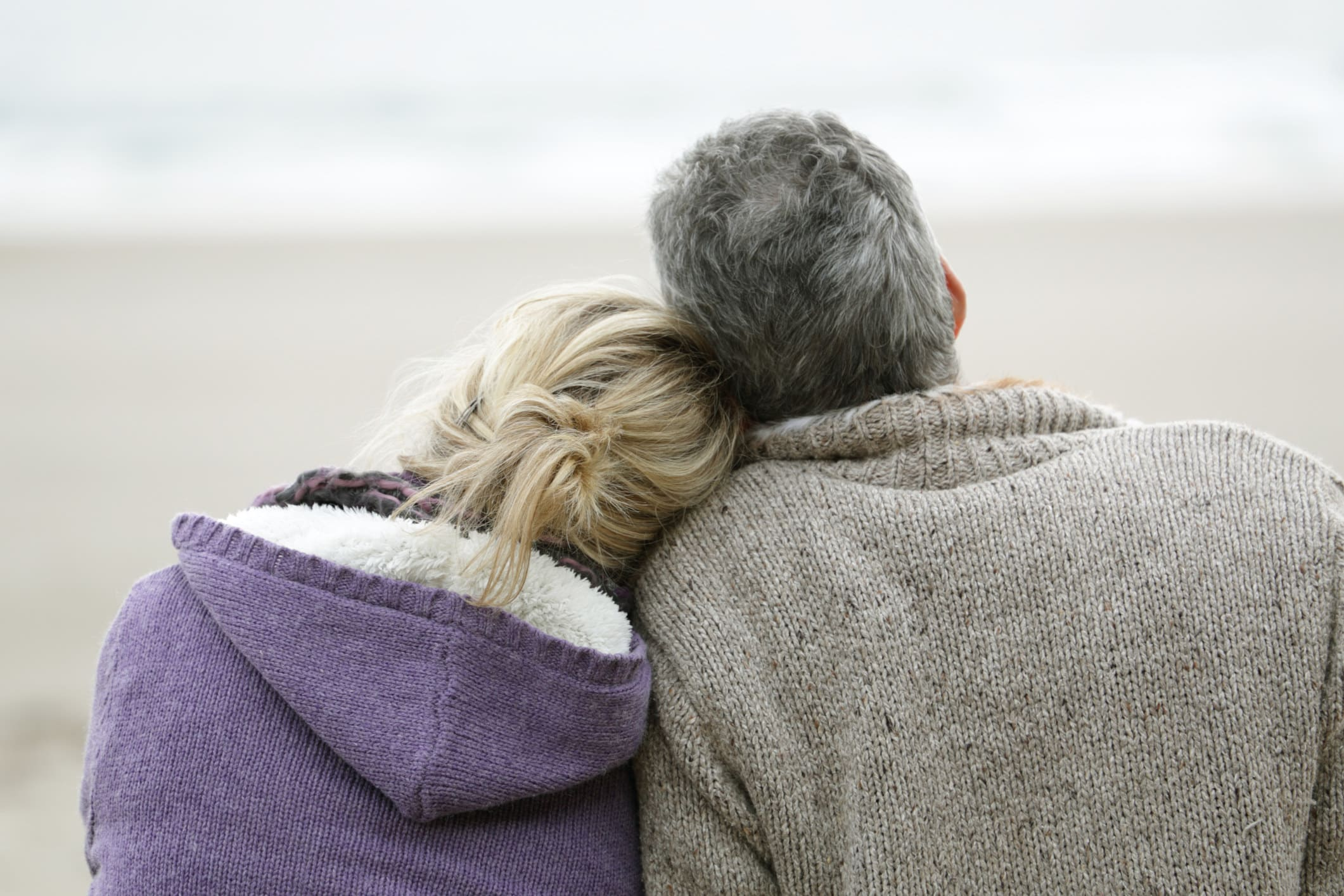 a couple leaning their heads on each other staring at the ocean