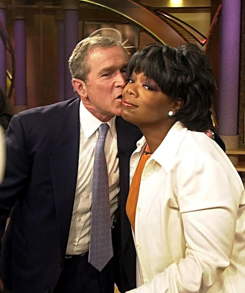 oprah getting a kiss on a cheek from prez bush