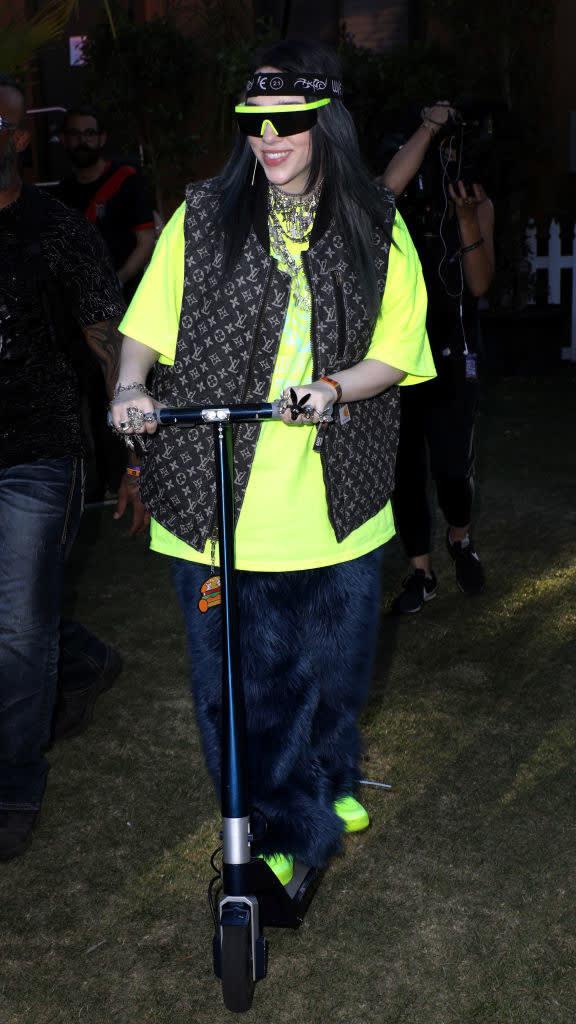 Billie com uma calça azul felpuda, camiseta verde neon e colete da Louis Vuitton andando de patinete