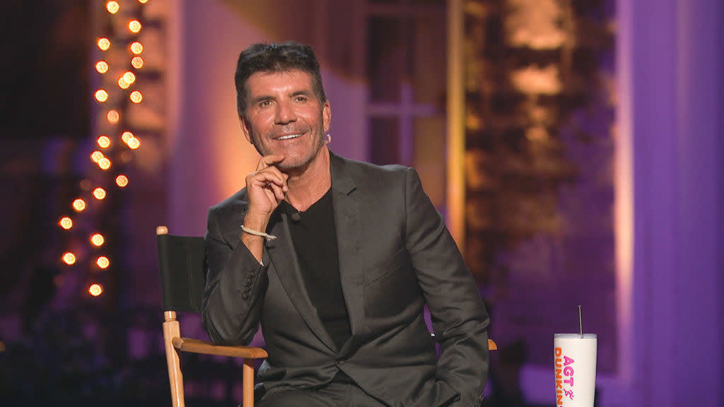 Simon Cowell smiles in his director's chair