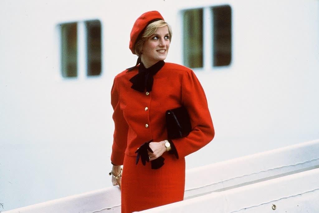 Princesa diana com um vestido vermelho, boina vermelha e um lenço preto no pescoço.