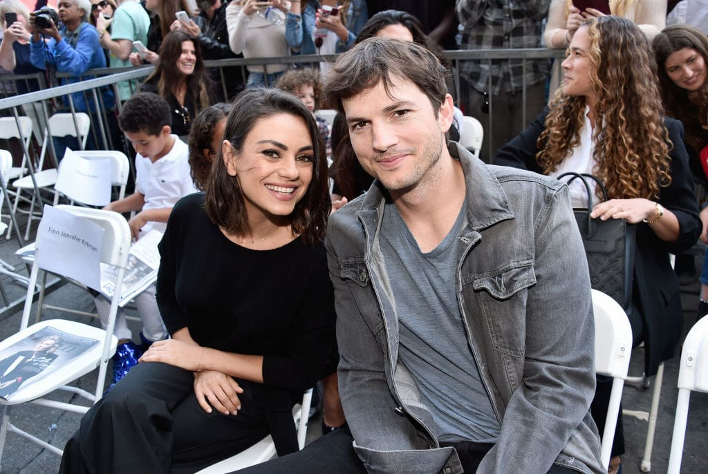 Mila and Ashton sitting together and smiling