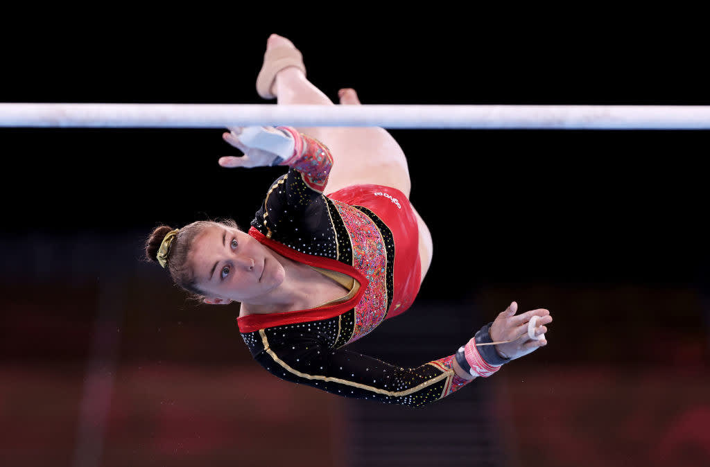 A gymnast reaching for the bar with one hand