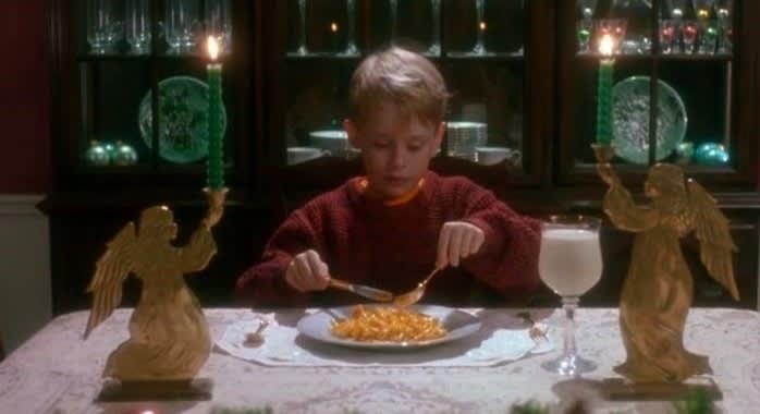"""Kevin, de """"Esqueceram de mim"""", jantando à mesa com uma taça de leite"""