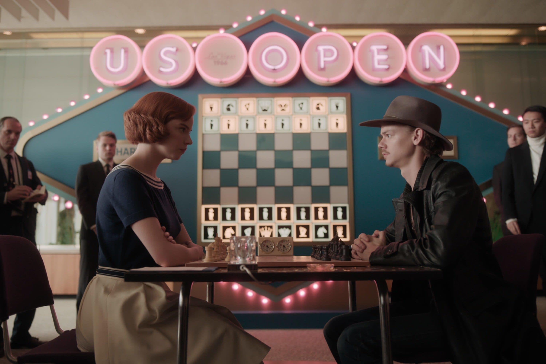 Beth e Benny se enfrentando numa partida de xadrez com pessoas assistindo