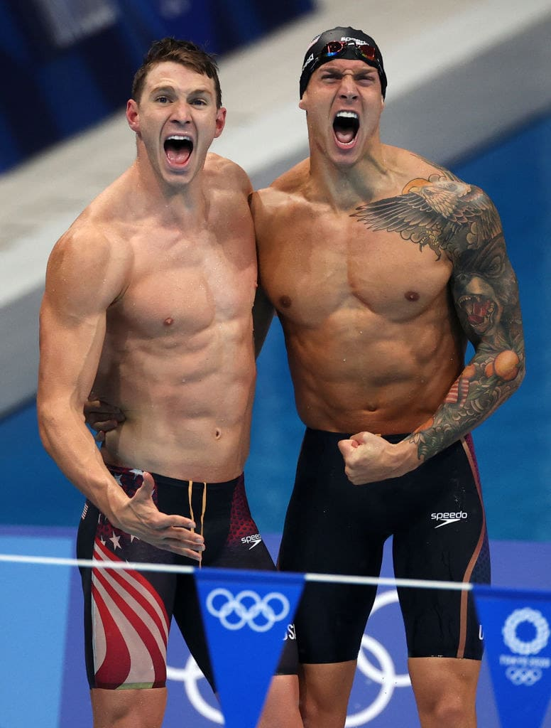 Two American swimmers cheering at the pool