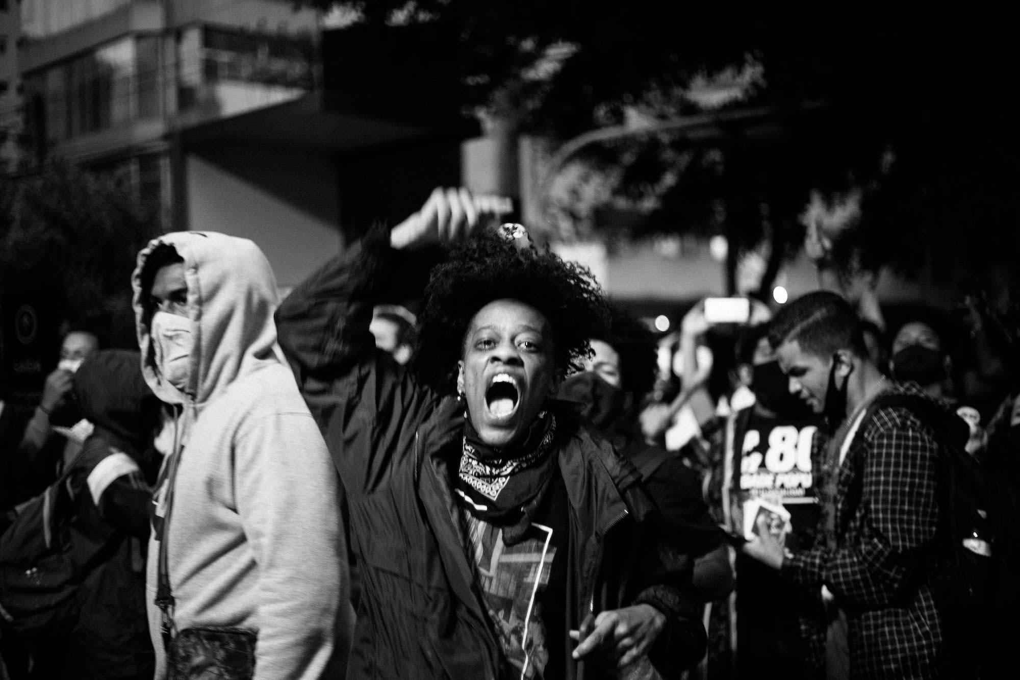 Cena de protesto com pessoas passando, uma pessoa em primeiro plano com bandana no pescoço, gritando e erguendo punho.