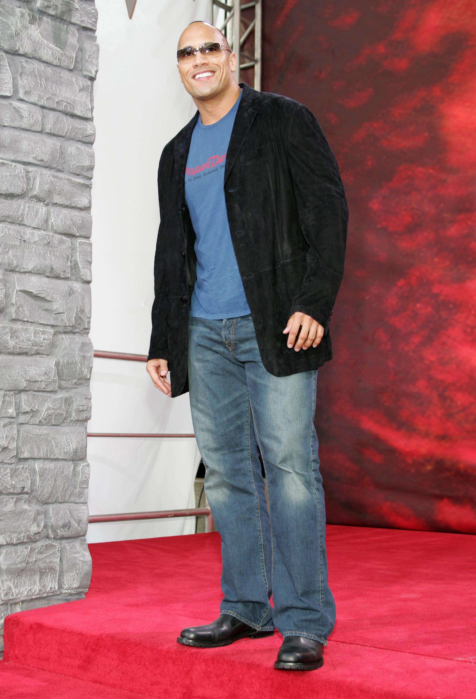 Dwayne wears a t-shirt, a blazer, jeans, and sunglasses.