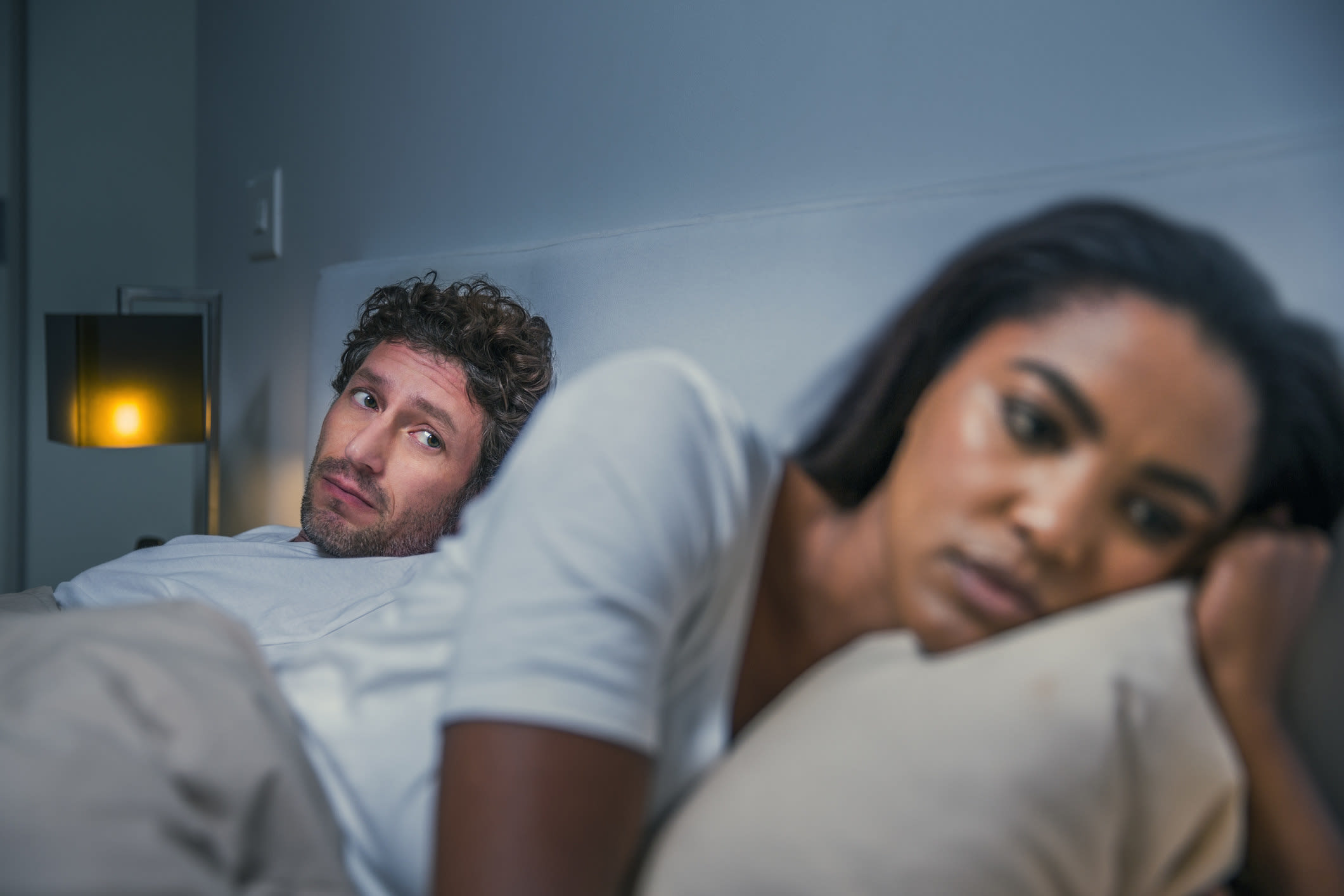 an unhappy woman looking away from her partner in bed