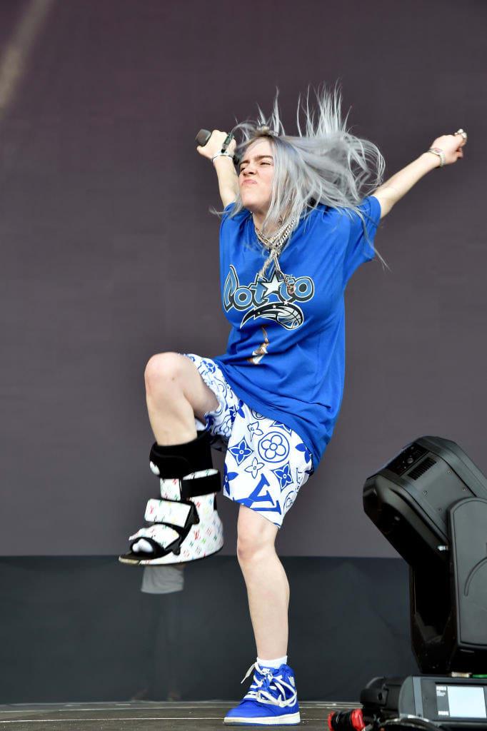 Billie no show com conjunto azul e bota ortopédica Louis Vuitton