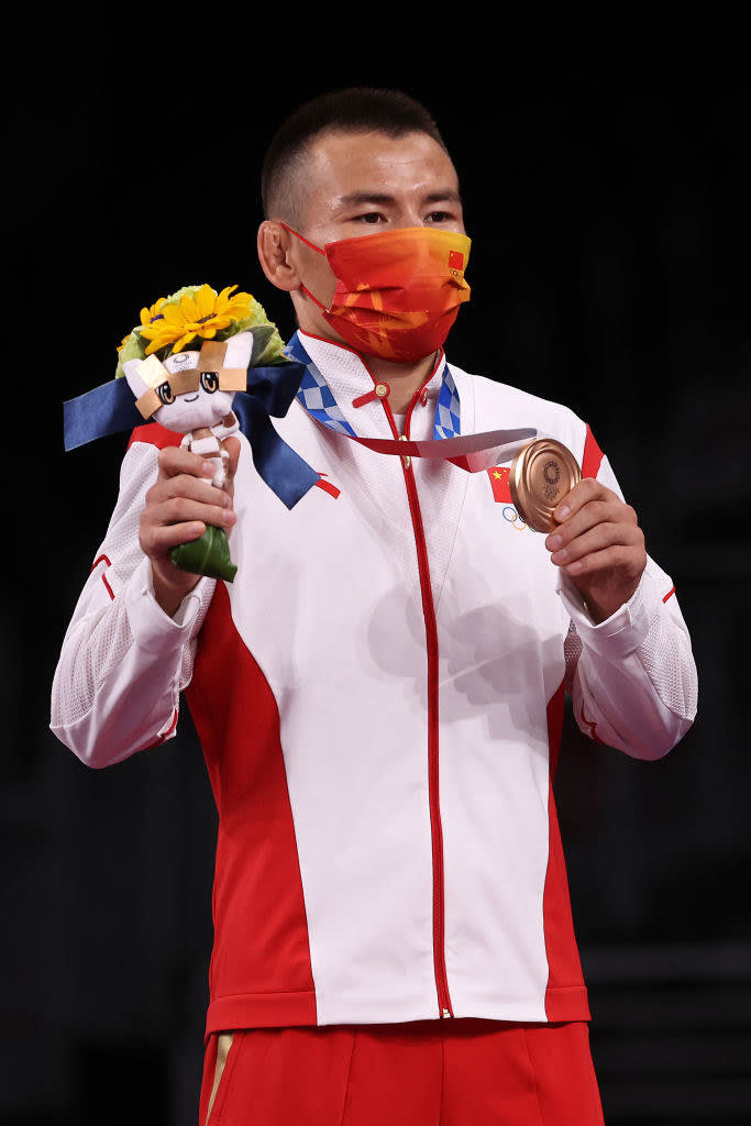 Sailike Walihan of Team China poses with the bronze medal and flowers during the Victory Ceremony
