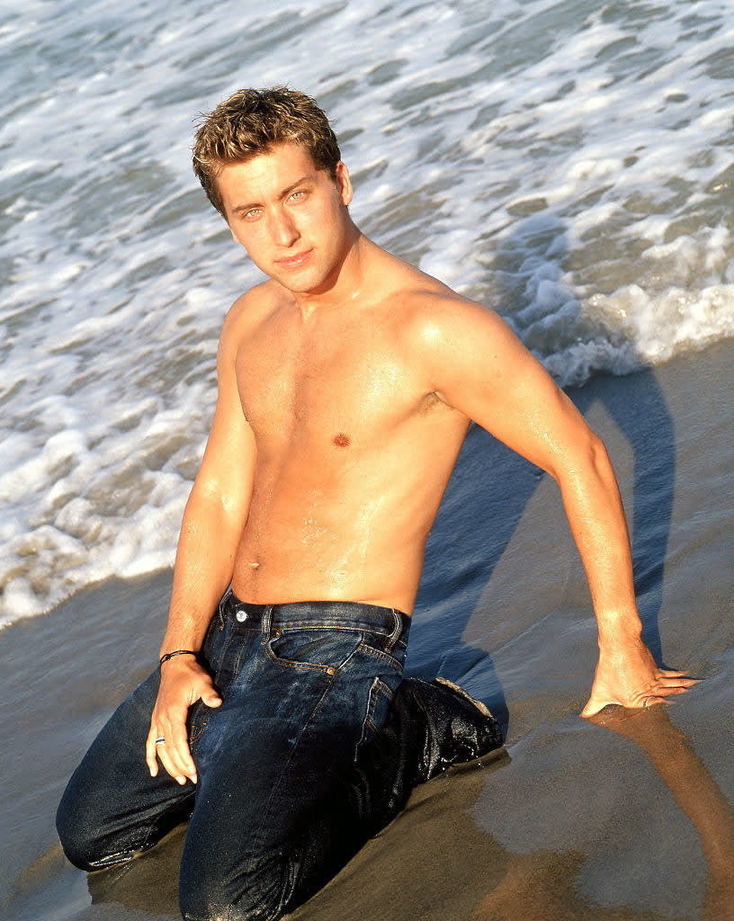 he's posing in jeans soaking wet on the beach