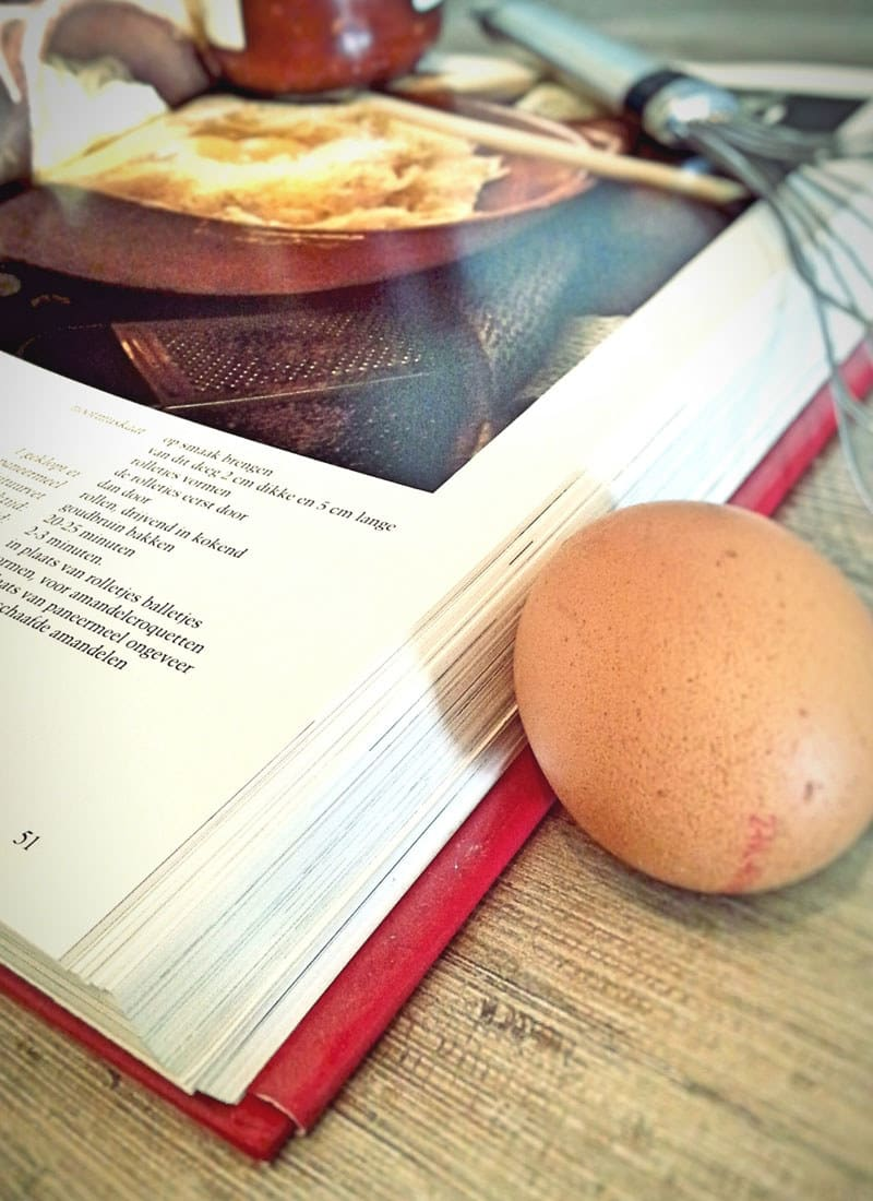 A cookbook and an egg resting next to it.