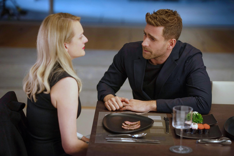 Imagem de Elisabeth Moss e Olver Jackson-Cohen no filme O Homem Invisível. Na cena, eles estão jantando.