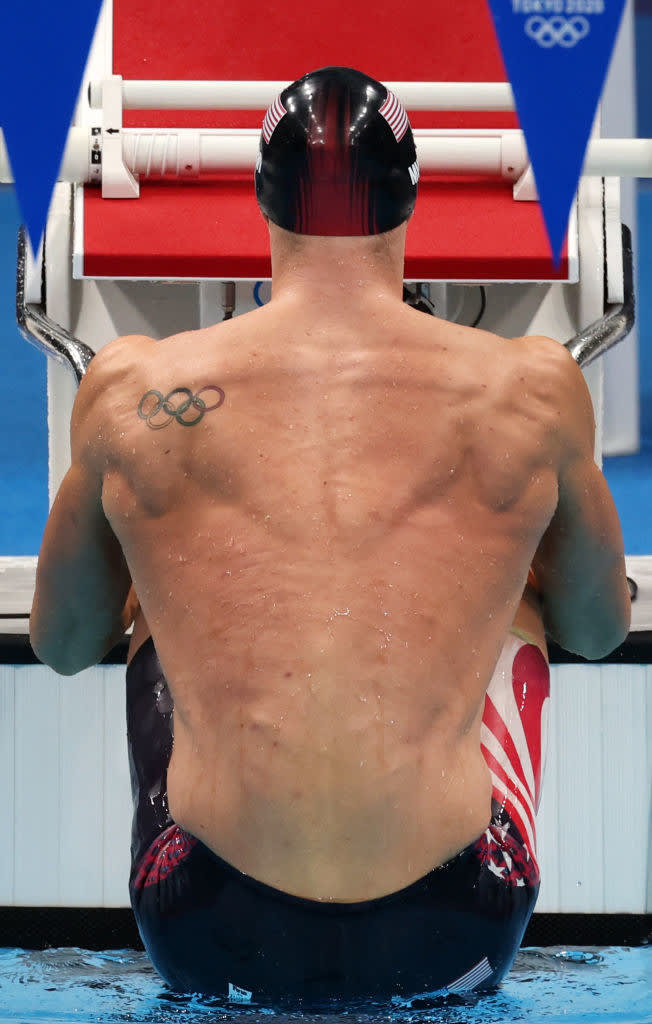 An American swimmer lifts himself out of the water as he prepares to launch for the start of a backstroke race