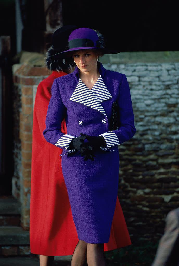 Diana usando um vestido roxo com um chapéu da mesma cor. A parte interna das mangas e da gola são listradas em preto e branco.